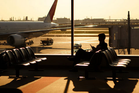 alternatives to working at your desk: a man sitting in an airport terminal near a window