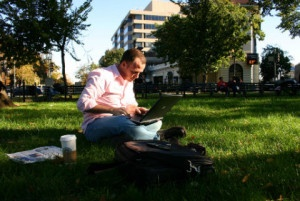 alternatives to working at your desk: a man sitting on grass with a laptop