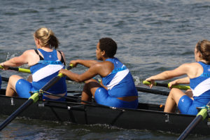 Three team members rowing in a boat, used for blog 4 lessons rowing can teach us about productivity management